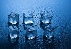 Ice cubes with water drops on blue background Stock Images