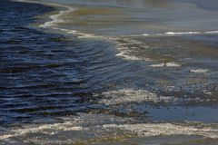 Ice on a dar water surface. Detail of a winter lake, dark rippling water and ice royalty free stock image