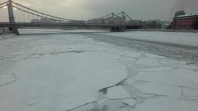 Ice drift on a megapolis river. Aerial view of a beginning ice drift on a wide megapolis river stock footage