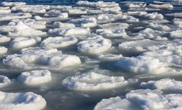 Ice drift on the river. White little ice floes float on the water. Early spring, thaw, melting snow. Soft sunlight Royalty Free Stock Images