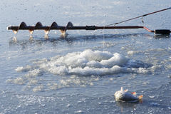Ice drill and ice fishing rod Royalty Free Stock Photo
