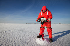 Ice drilling. Ice fisherman drilling a hole with a power auger on a frozen lake Royalty Free Stock Photo
