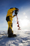 Ice drilling. Ice fisherman drilling a hole with a power auger with sun flares Royalty Free Stock Images