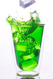 Ice drop to glass of green water Stock Photo