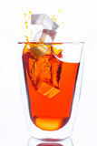 Ice drop to glass of orange water. Royalty Free Stock Photography