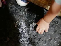 Ice on the dusty floor about to be picked and eaten by a baby stock photos