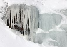 Ice Falls. Landcape image of ice stalactites like formation, created by melting snow over boulders Stock Photo