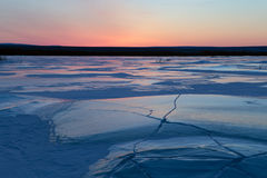 Ice field in cracks and red sky. Stock Photo