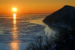 Ice and fiery sunset #2. Sunset over Okhotsk Sea with a view of the island Stock Image