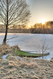 Ice filled boat and sunrise. Boat filled with ice at the edge of a snow covered and frozen over lake. It is early spring in Sweden. The sun rises behind a small Royalty Free Stock Photos