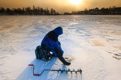 Ice fisher with ice auger Stock Images
