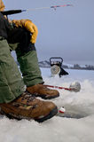 Ice fisherman fishing in ice hole and equipment. A close up of an ice fisherman float fishing in an ice hole and equipment on an arctic frozen lake Royalty Free Stock Image