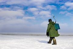 Ice Fisherman going away. Ice fishing - very popular winter hobby in Estonia, Latvia, Lithuania, Russia etc Stock Photography