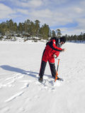 Ice fisherman with a hand ice auger. INARI, FINLAND - APR 2, 2015: Preparation for ice fishing on the Lake Inarijaervi. Ice fishing is the practice of catching Stock Photos
