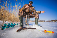 Ice fisherman with pike caught on a tip up Stock Photo