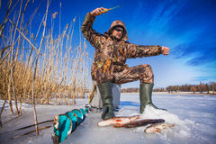 Ice fisherman with pike caught on a tip up Royalty Free Stock Photos