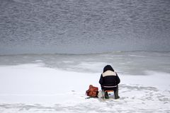Ice fisherman on winter mountain lake fox fur . stock image