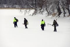Ice fishermen. Firhermen preparing to fish on river covered with thick ice Stock Photo