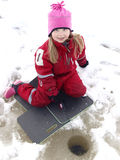 Ice fishing. Little girl is ice fishing on a lake Royalty Free Stock Photo
