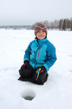 Ice fishing. Boy ice fishing on lake in winter Stock Photos