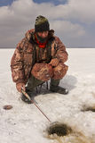 Ice fishing. A man catches a fish on ice fishing royalty free stock image