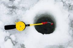 Ice fishing. Rod and hole Royalty Free Stock Image
