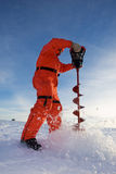 Ice fishing. Ice fisherman drilling a hole with a power auger Stock Images