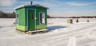 Green and Blue Ice Fishing Cabins in Ste-Rose Laval. Ice Fishing cabins in a vast spaces on the frozen Rivière des Mille Îles in Ste-Rose, Laval, Quebec Royalty Free Stock Photography