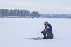 Ice fishing. Fisherman sitting on a frozen lake for fishing royalty free stock photos