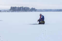 Ice fishing. Fisherman sitting on a frozen lake for fishing royalty free stock photography