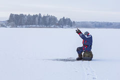 Ice fishing. Fisherman sitting on a frozen lake. For fishing stock photo