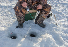 Ice fishing. Fisherman sitting with fishing rod in front of the two holes royalty free stock photography