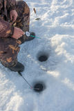 Ice fishing. Fisherman sitting with fishing rod in front of the two holes stock photo
