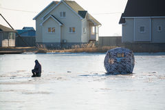Ice fishing on frozen lake. Fisherman sitting on some distance from his tent Royalty Free Stock Images