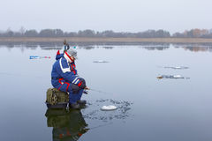 Ice fishing. On a frozen lake with a layer of water royalty free stock photography