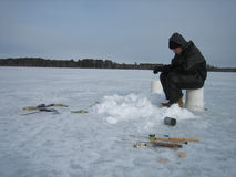 Ice Fishing on a Frozen Lake. A man sitting on a bucket ice fishing on a frozen lake royalty free stock photography