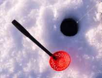 Ice fishing hole with a scoop for removing slush Royalty Free Stock Photo