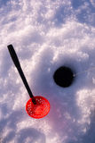 Ice fishing hole with a scoop for removing the slush Stock Image