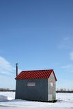Ice fishing hut under the blue sky. Ice fishing hut with red roof and chimney under the blue sky stock photos