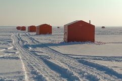 Ice fishing huts on a frozen lake in Ontario at sunset stock images