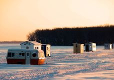 Ice fishing huts on a frozen lake at sunset with a completely clear orange sky. By the forest Stock Image