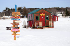 Ice Fishing Huts in winter time. Signs and Ice Fishing Shacks on a Frozen Lake Squam, New Hampshire Royalty Free Stock Image