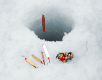 Ice fishing lures. Several ice fishing lures around ice hole Royalty Free Stock Photos