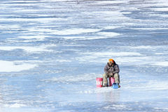 Ice Fishing. A man braving the frigid cold temperatures to ice fish stock photography
