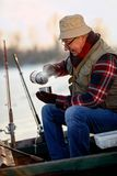Ice fishing. senior man sitting on frozen lake and drink tea. Ice fishing. senior man on frozen lake and drink hot tea Stock Images
