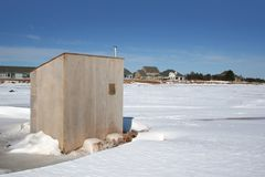 Ice Fishing Shack. An ice fishing shack on the harbour in front of some new homes stock images