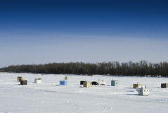 Ice Fishing Sheds. Scattered shacks used for ice fishing situated on the frozen Red River in Manitoba Royalty Free Stock Images