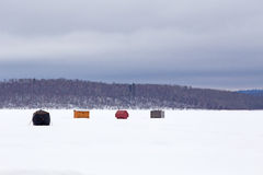 Ice fishing shelters on snow covered lake Stock Photography