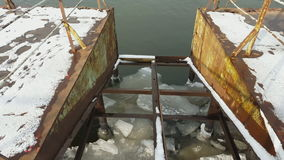 Ice floating on river in spring time under old pier. Steadicam shot stock video footage
