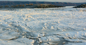 Ice Floe Behind Gravel Bar. An ice floe is jammed up against a gravel bar on its way to the sea Royalty Free Stock Photos